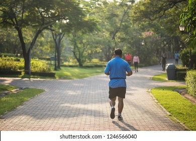 Senior old fat man running or jogging in park at sunrise with natural background. Elderly guy exercise or work out. Sport and health care lifesytle concept.