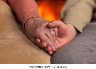 Senior old hands holding in front of fireplace - closeup, commitment and resilience concept