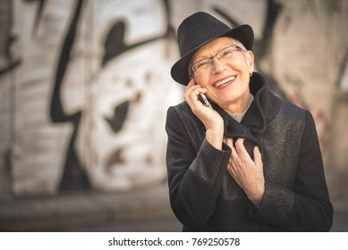 Senior old lady dressed classy and smartly, having a pleasant and happy conversation over her smart phone in the street