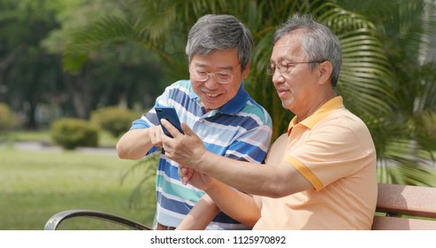 Senior old male friends chatting together at outdoor park, showing photo on cellphone to other