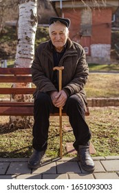 Senior old man caucasian pensioner grandfather holding his cane on the sitting on the bench by sidewalk pavement in park sunny winter or spring day looking to the camera wearing coat jacket and hat