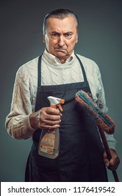Senior old man disgusted by the idea of cleaning, holding cleaning chemicals and wearing apron