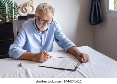 Senior old man elderly examining and signing last will and testament