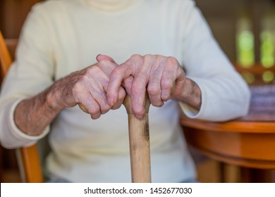Senior old man hands on walking stick  close-up.