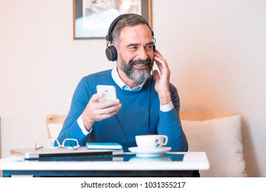Senior old man listening to his favorite music through big headphones, enjoying the rich sound of the music, he's sitting in a coffee shop