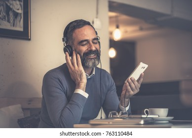 Senior old man listening to his favourite music through big headphones, enjoying the rich sound of the music, he's sitting in a coffee shop