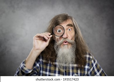 Senior old man looking through zoom magnifying glass. Funny elder amazement investigation or test vision loss