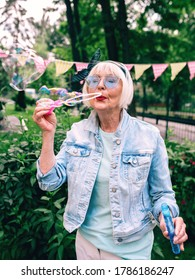 senior (old) stylish woman with gray hair and in blue glasses and denim jacket blowing bubbles outdoors. Holidays, party, anti age, fun concept