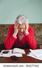 Senior old woman desperate over the bills she has to pay, worried and with headache
