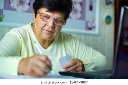 c483918d52 Senior old woman in eyeglasses checking costs of daily expenses on laptop  at home. White