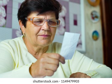 95d5e001b8 senior old woman in eyeglasses checking costs of daily expenses at home.  Blurred white caucasian