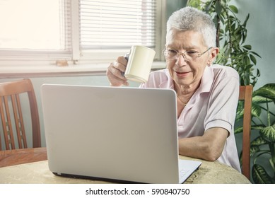 Senior old woman having her morning coffee while using her laptop computer