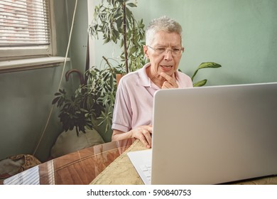 Senior old woman having troubles using her computer