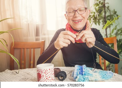 Senior old woman knitting a sweater, enjoying her free time, practicing her hobby