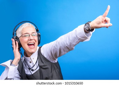 Senior old woman listening to her favorite music through big headphones, enjoying the rich sound