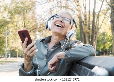 Senior old woman listening to her favourite tunes, outside at the park, enjoying the rich sound, smiling and having fun