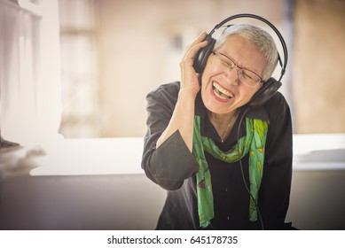 Senior old woman listening to her favourite music through big headphones, enjoying the rich sound