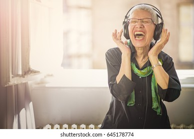 Senior old woman listening to her favourite music through big headphones, enjoying the rich sound