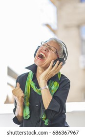Senior old woman listening to her favourite music through big he