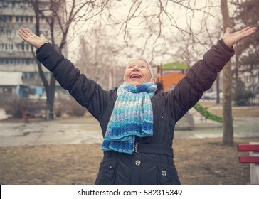 Senior old woman raising hands in the air, celebrating life