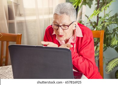Senior old woman sending love and kisses to her family over Skype or Viber using her laptop