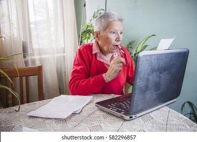 Senior old woman in shock with her monthly statement, looking at bills at disbelief while using her laptop