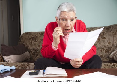 Senior old woman shocked with the bills she receives, appalled and surprised