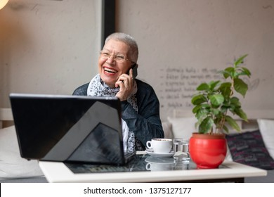 Senior old woman sitting in a coffee shop and having a nice chat over her cell phone