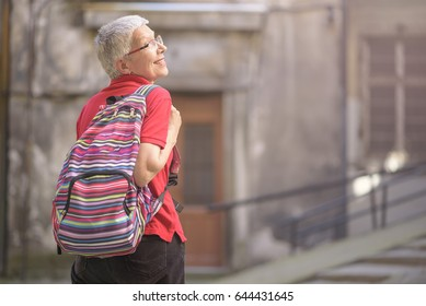 Senior old woman tourist with a backpack preparing to leave her home to go traveling