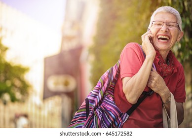 Senior old woman, a tourist in a foreign city, talking on her phone with her family, laughing cheerfully