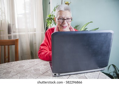 Senior old woman using her laptop at her home