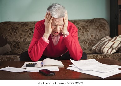 Senior old woman worried with the bills she has to pay, no money to cover expenses