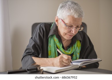 Senior old woman writing down letters on a piece of paper, recor