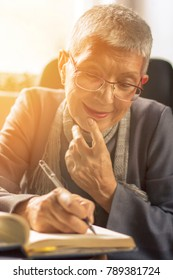 Senior old woman writing down letters on a piece of paper, recording a journal or diary entry or writing a novel
