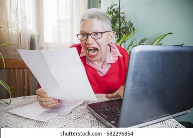 Senior old woman yelling at bills while using a computer, overreacting to her expenses