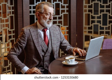 Senior old-aged business man in expensive bespoke man having coffee in a coffee shop and working on his laptop