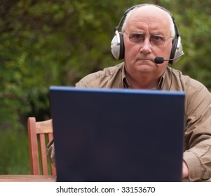 senior older male man learning to use a pc laptop computer and headphones mic for voip internet calling over wifi. elderly man outside in garden with laptop computer and headphones