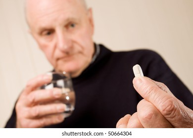Senior older man holding tablet or pill on one hand and a glass of water