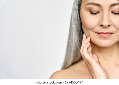 Senior older middle aged Asian woman with grey hair and radiant face with perfect skin. Advertising of rejuvenating skincare and makeup for natural radiant glow and healthy skin. Copy space.