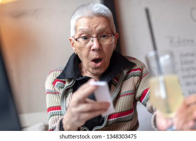 Senior older woman in a cafe shocked by the price she has to pay for her order