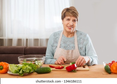 Senior or older woman cooking salad in kitchen is looking at camera. Healthy food concept. Healthy lifestyle.