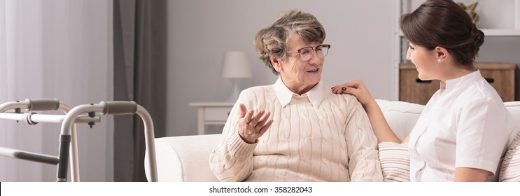 Senior older woman talking with female young caregiver
