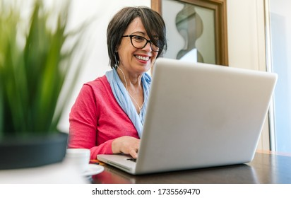Senior older woman working with laptop computer on the table at home indoor. Old mature people and technology concept
