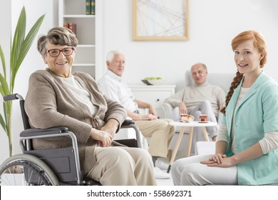 Senior on a wheelchair with young nurse