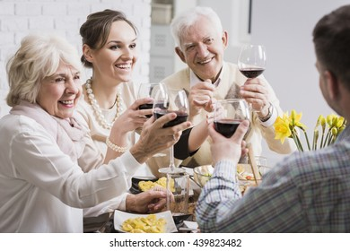 Senior parents an adult daughter toasting red wine glasses