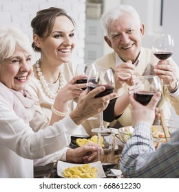 Senior parents and adult daughter toasting her promotion with red wine during elegant lunch