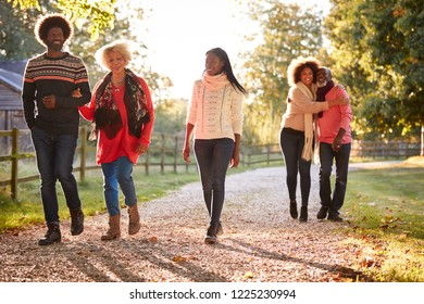 Senior Parents With Adult Offspring Enjoying Autumn Walk In Countryside Together