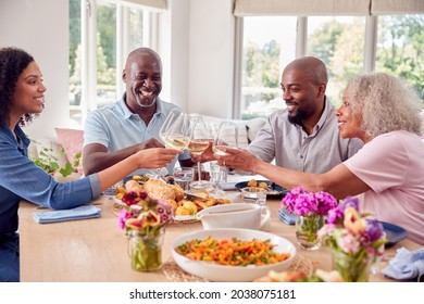 Senior Parents With Adult Offspring Making Toast Sitting Around Table For Family Meal