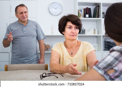 Senior parents attentively listening and talking to adult daughter indoors