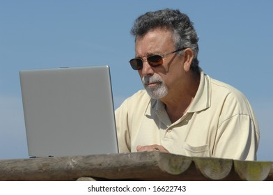 senior in a park with laptop computer
